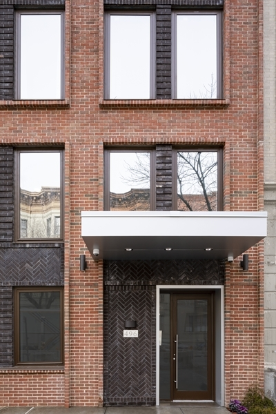 The stately facade of beautiful running bond brick with inserts of herringbone brick is perfectly complimented by tall casement aluminum window frames with insulated glass.