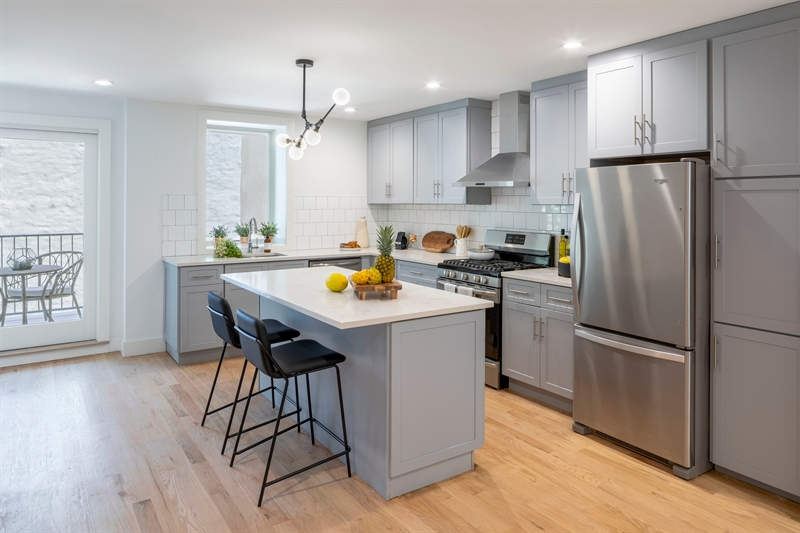 Kitchens are ready for entertaining with custom cabinetry sourced in Brooklyn, sleek quartz countertops and classic tiled backsplash.