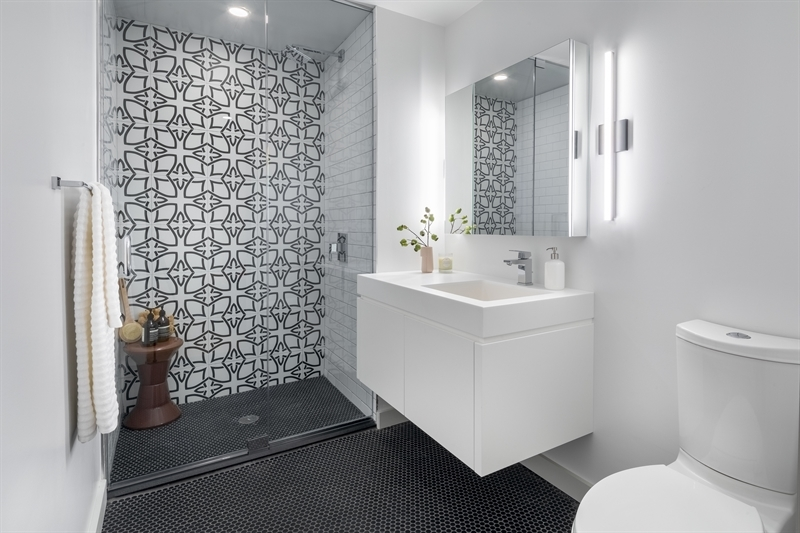 The spacious master bathroom showcases stylish Vanguard tile and classic subway tile paired with Matte black penny tile floors, creating a sophisticated, yet calm, design.