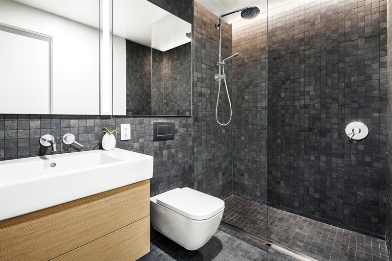 The sleek, modern bathrooms feature anthracite porcelain mosaic tile, oak vanities, and Grohe chrome fixtures.