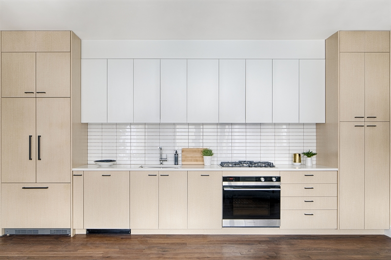 Custom kitchen cabinets and white quartz countertops are paired beautifully with a white high gloss subway tile backsplash for simple elegance. Kitchens are completed with a Fisher and Paykel and Bosch appliance package.