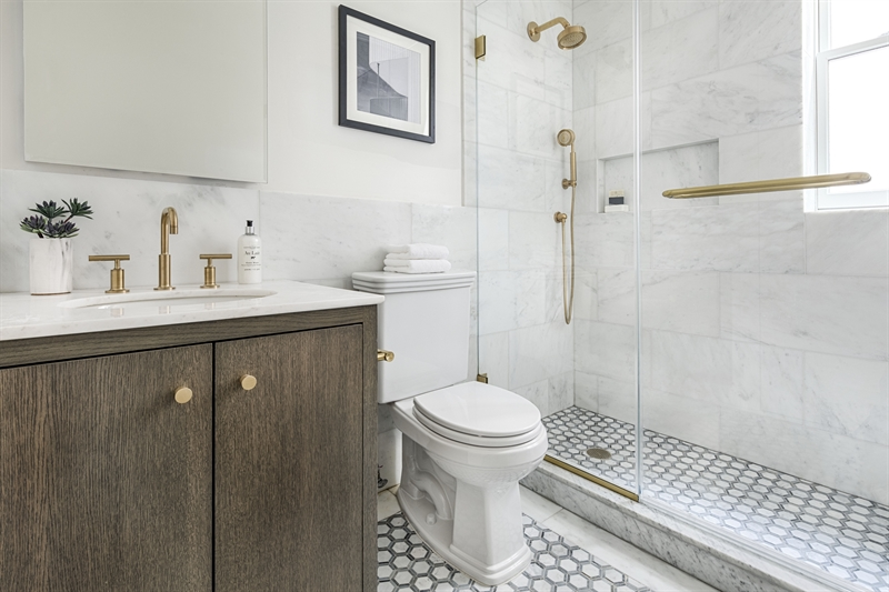 Serene baths feature Bianco Carrara marble, custom vanities and Kohler fixtures.