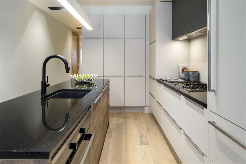 The custom Nobilia kitchen has an abundance of storage space in icy grey cabinetry. The at home cook will appreciate a vented hood over a Miele 5-burner gas cooktop surrounded by white quartz. A Miele wall oven, Miele dishwasher, Bosch microwave and Liebherr Refrigerator complete the package.