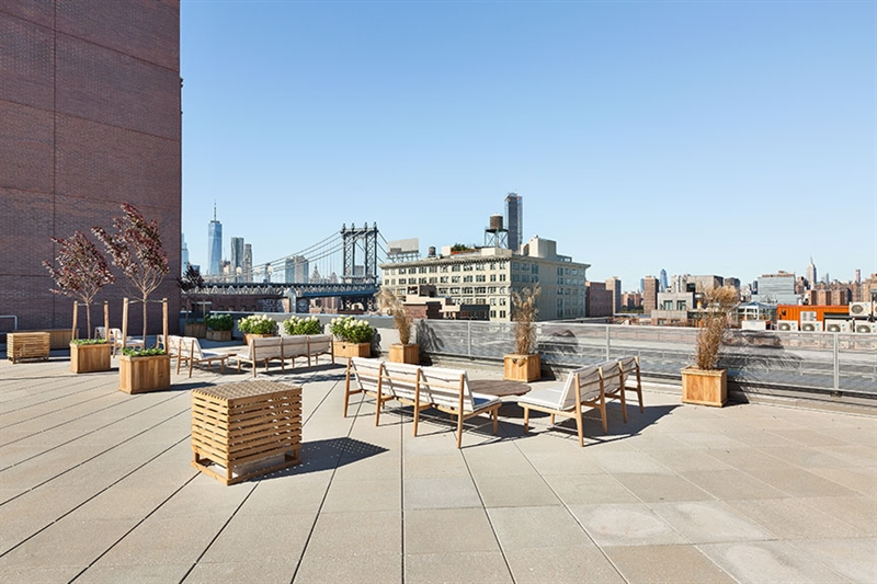 Amenities include a large communal rooftop terrace featuring panoramic views of Manhattan and the East River